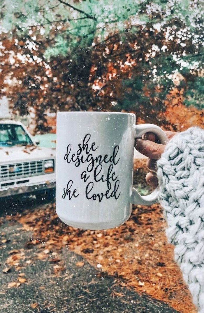 she designed a life she loved written on white mug cute fall backgrounds held by woman fall leaves in the background