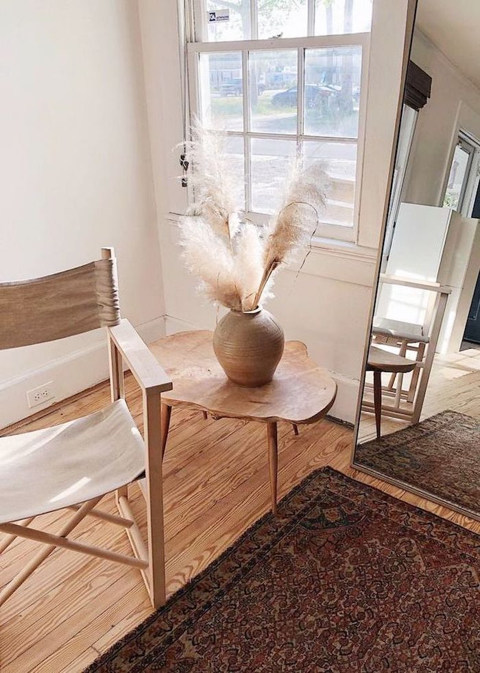 tall mirror where to buy pampas grass wooden chair and side table next to it ceramic vase with pampas grass