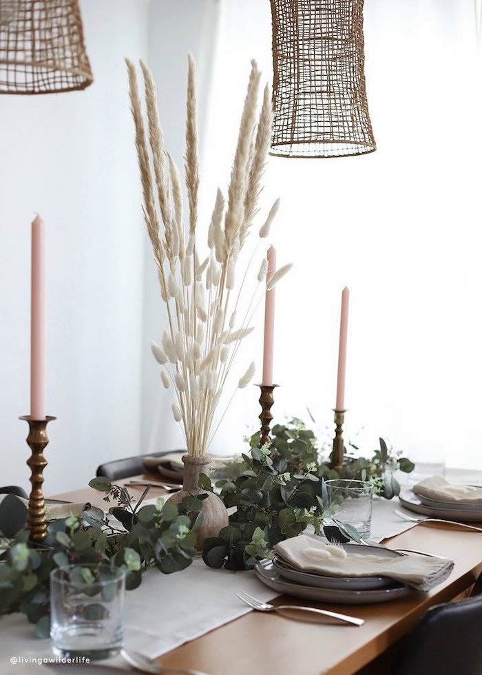 tall pampas grass in the middle of white table runner on wooden table three candles greenery on it