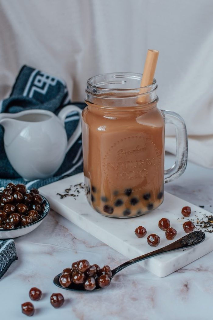 tapioca pearls scattered across the table bubble tea recipe glass full of boba tea with plastic straw placed on marble board