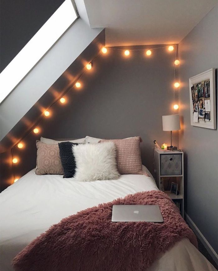 teenage girl bedroom ideas gray walls bed with pink fluffy blanket pink throw pillows fairy lights on gray walls