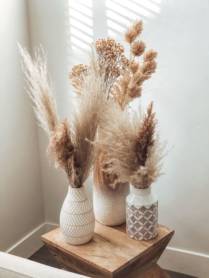 three ceramic vases filled with pampas grass placed on small wooden table white wall in the background