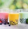 three plastic cups filled with pink yellow green bubble tea fruits scattered around them what is boba