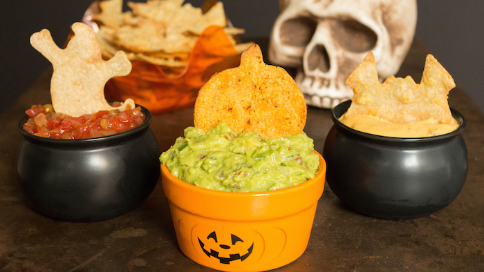 three small bowls in black and orange with different dips inside tortilla chips on top halloween snack ideas salsa guacamole