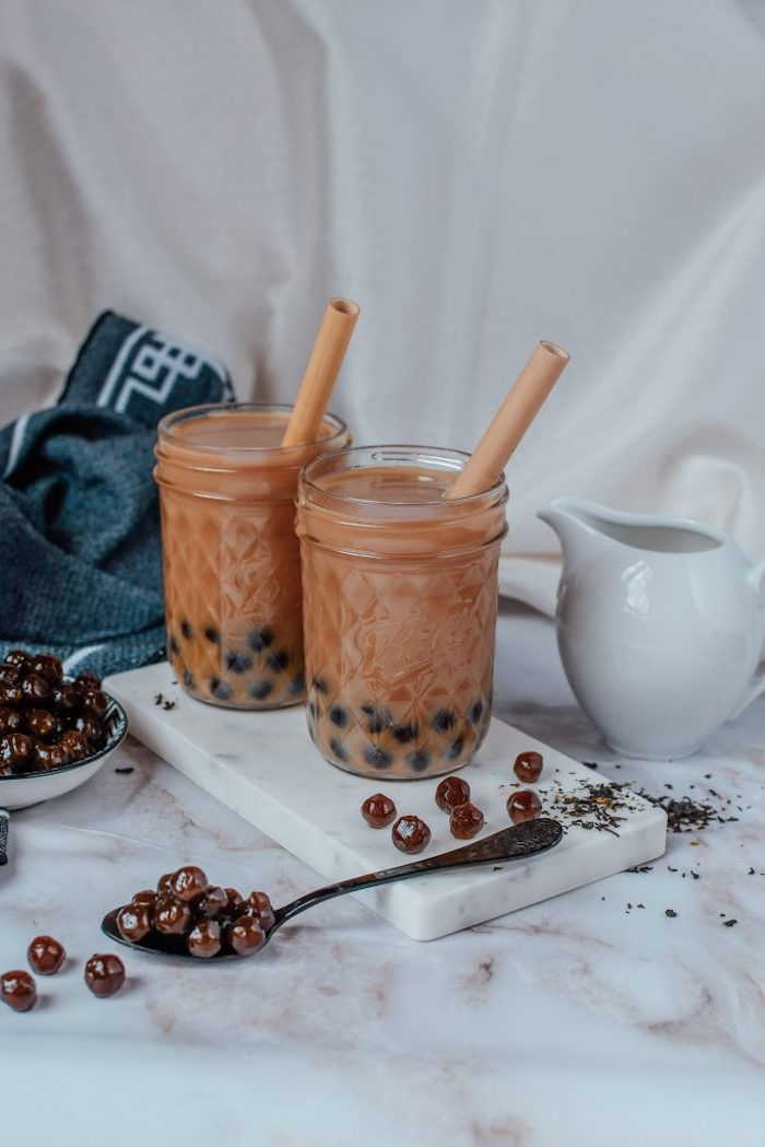 two glasses filled with boba tea with plastic straws placed on marble board bubble tea recipe scattered tapioca pearls around the glasses