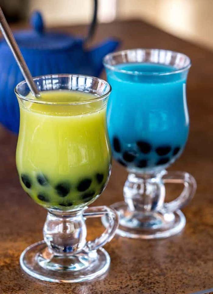 two glasses with green and blue bubble tea steel straw how to make boba placed on brown granite surface