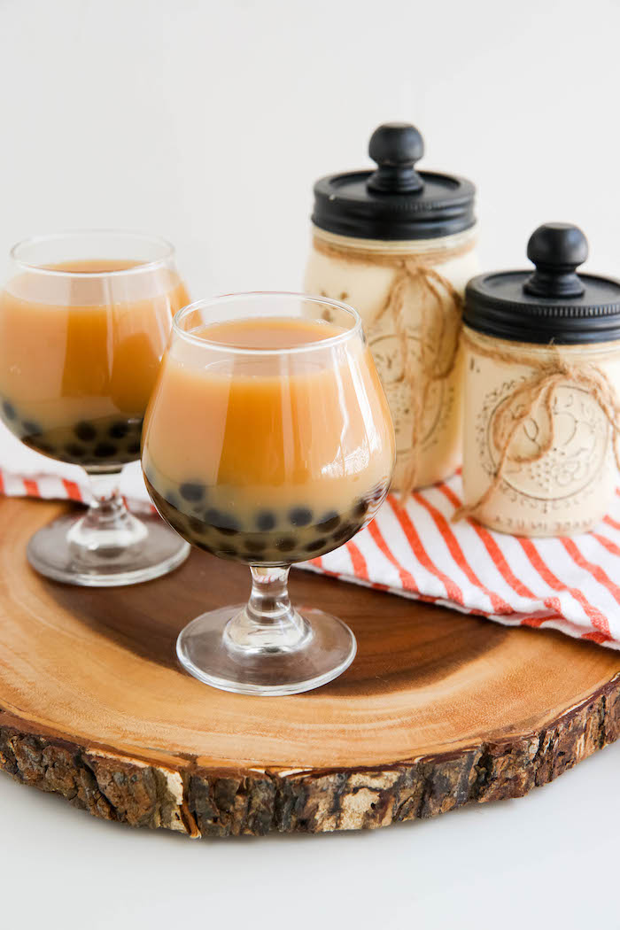two glasses with keto bubble tea how to make boba tea tapioca pearls on the bottom of the glasses placed on wooden log