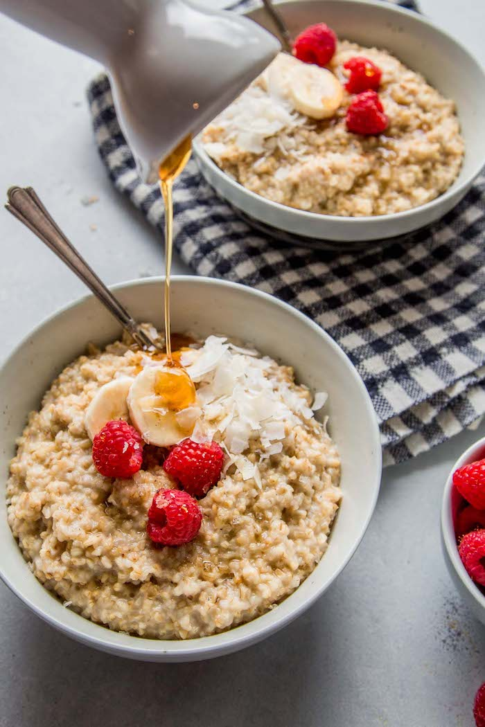 two white bowls filled with oatmeal with bananas raspberries shredded coconut healthy pressure cooker recipes honey poured over