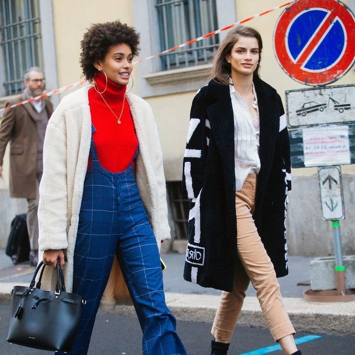two women walking down the street wearing different outfits pinterest cute outfits blue onesie with red polo sweater beige trousers with white shirt black coat