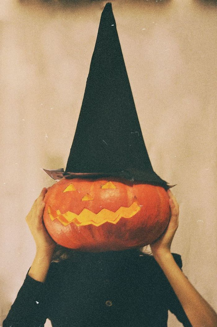 vintage photo of woman dressed in a witch costume halloween desktop wallpaper carved pumpkin in front of her face witch hat on top of ther head