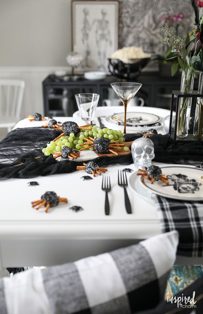 white table decorated with black tulle halloween party appetizers wooden cutting board with spider cheese balls grape