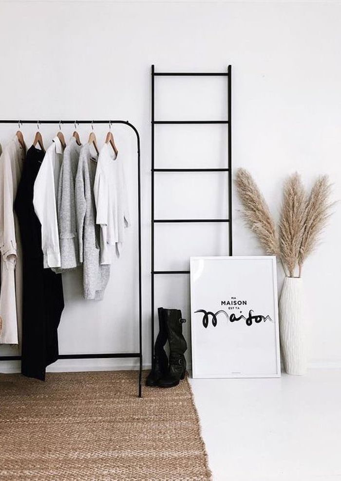 white walls behind black metal railing with coats hanging on it dried pampas grass inside white tall vase