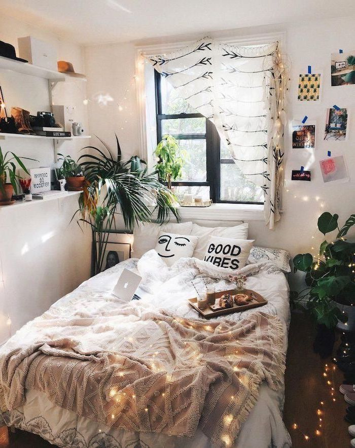 white walls with shelves and photos on them cute room ideas bed in the middle of the room with white throw pillows fairy lights hanging from the window