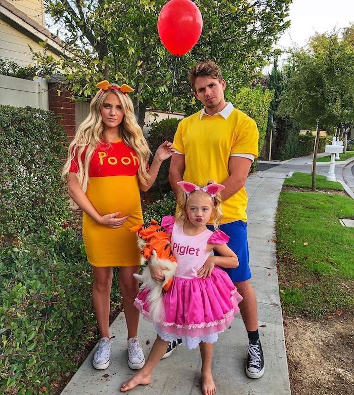 winnie the pooh piglet and christopher robin family halloween costume ideas family standing on sidewalk mom pregnant holding red balloon