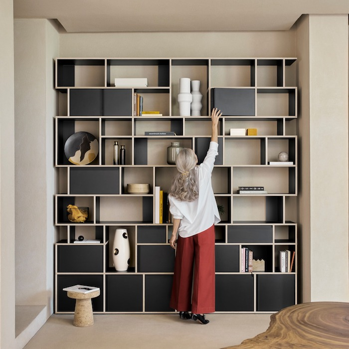 woman reaching opening a cabinet on black wooden bookshelf bookcase ideas shelves in different shapes