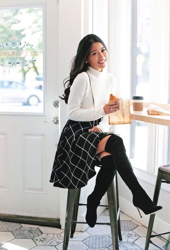 woman sitting in a coffee shop cute outfits for women wearing black skirt white polo sweater black knee high velvet boots