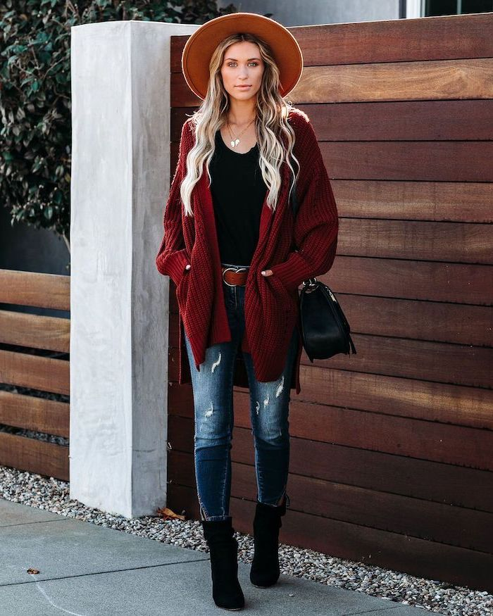 woman with long blonde wavy hair womens fall fashion wearing jeans black top red cardigan black boots and bag standing on the sidewalk