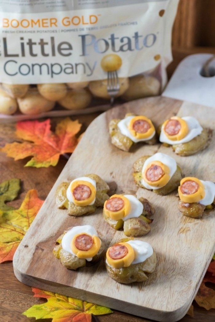 wooden cutting board on wooden table halloween appetizer ideas monster eye balls made with potatoes cheese sausages arranged on top