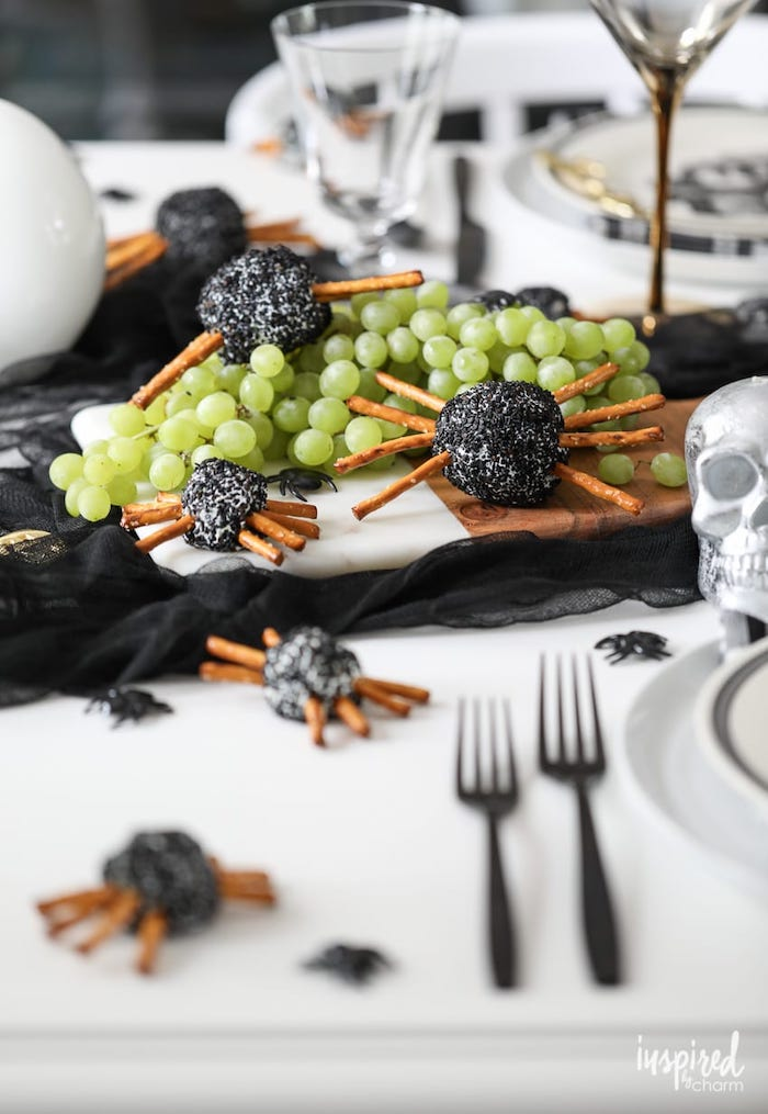 wooden cutting board placed on table with black tulle on it halloween party appetizers cheeseballs with pretzels arranged as spiders