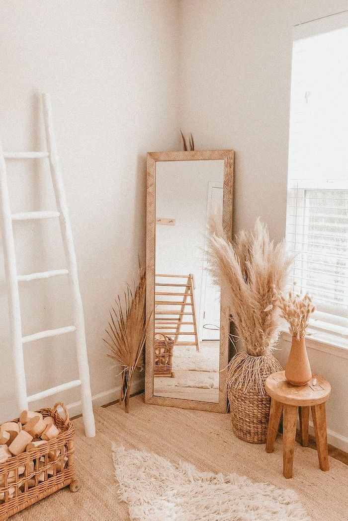 wooden floor white walls tall mirror surrounded by wooden vases and chair where to buy pampas grass