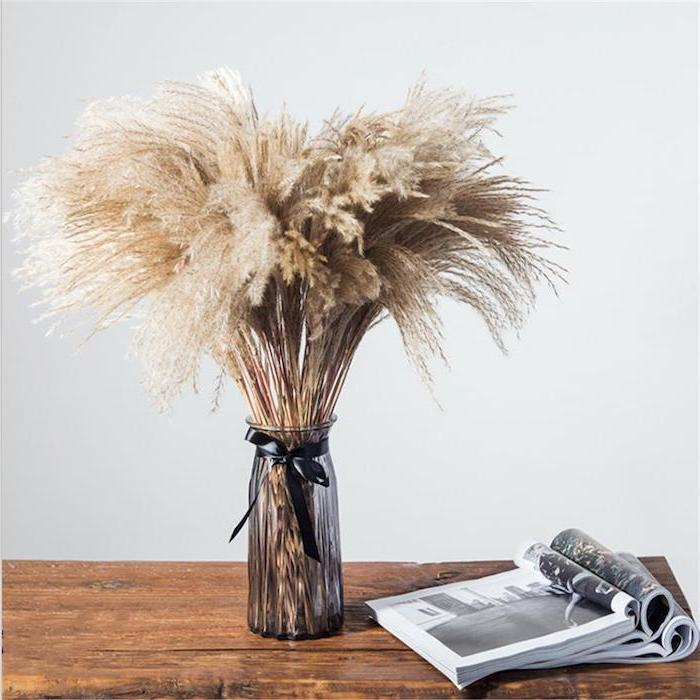 wooden table with open magazines on it glass vase with artificial pampas grass black bow tied around it