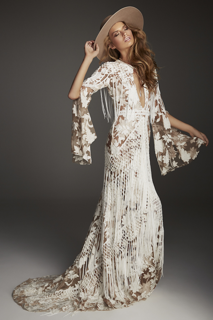 all lace long dress with fringe and long flounce sleeves boho lace wedding dress worn by woman with long dark blonde hair