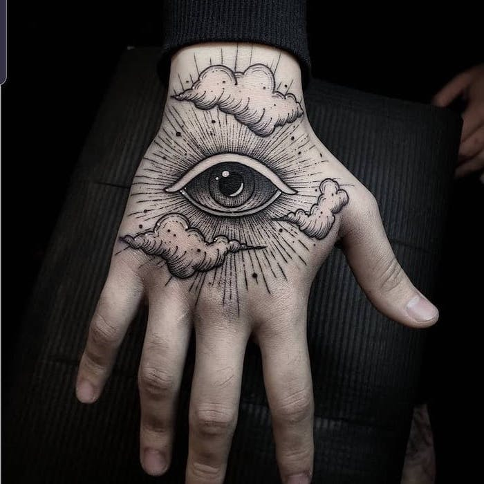 all seeing eye with clouds hand tattoo on man wearing black blouse tattoos with meaning of life black background