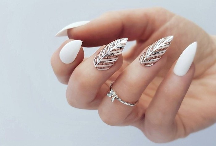 almond shape with pointed ends cute acrylic nail ideas white nail polish gold and silver feather decorations on middle and ring fingers