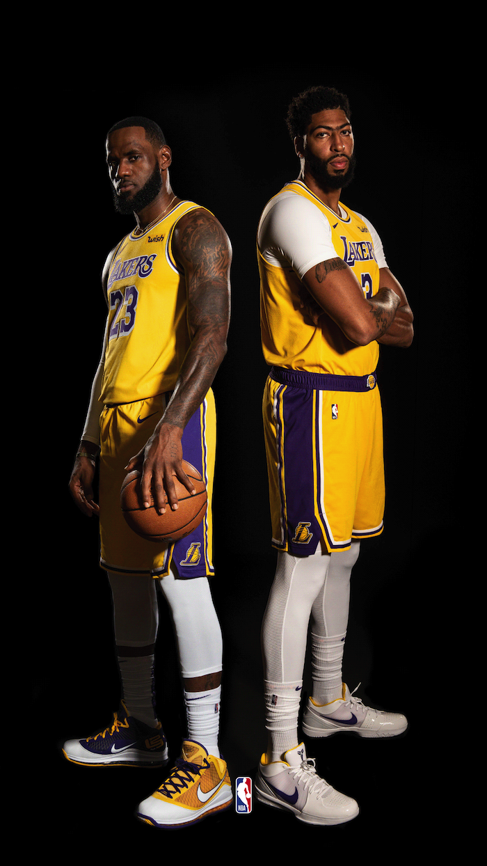 anthony davis and lebron james wearing gold lakers uniforms nba wallpaper iphone standing next to each other on black background