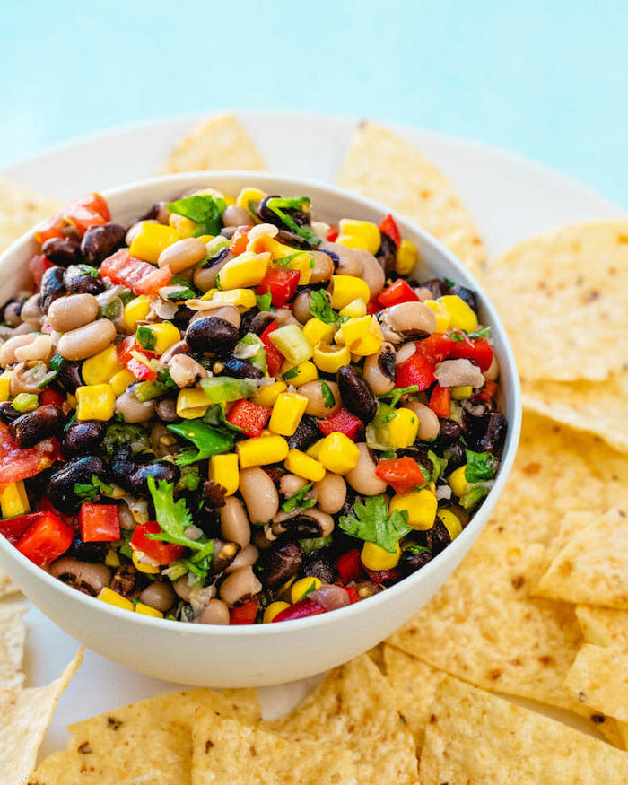 baked beans with corn peppers tomatoes chopped parsley in white bowl vegan party food tortilla chips around the bowl