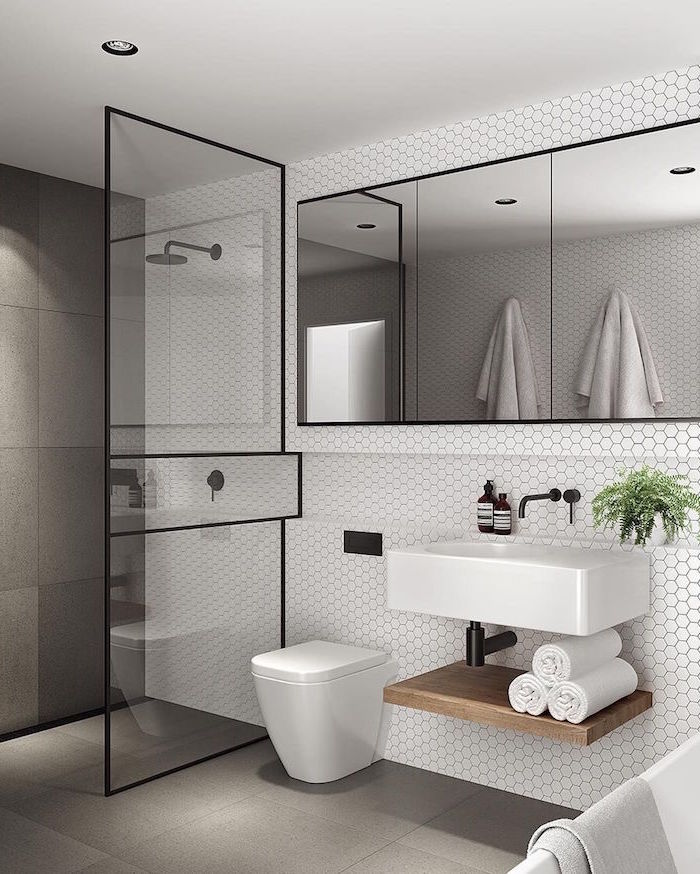 bathroom design with white honeycomb tiles floating vanity with large mirror above it scandinavian design shower separated with glass