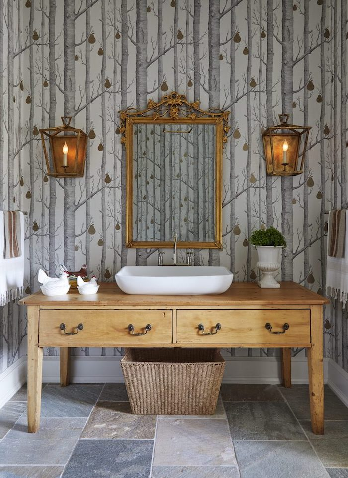 bathroom wooden vanity with sink mirror above it hanging on a wall with wallpaper with trees bathroom decor signs vintage lamps on both sides of the mirror