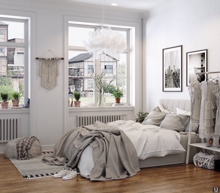bedroom design with white walls clothing rack black and white photos hanging on the wall above the bed scandinavian design wooden floor