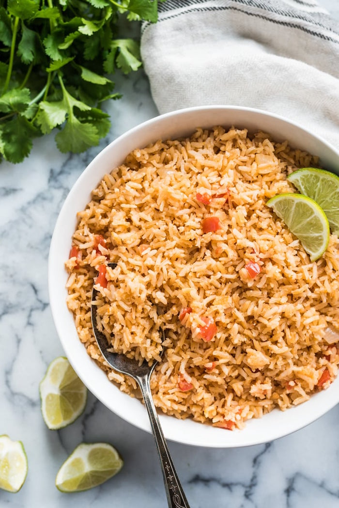 best mexican dishes mexican rice with tomatoes inside white ceramic bowl with lime slices on the side