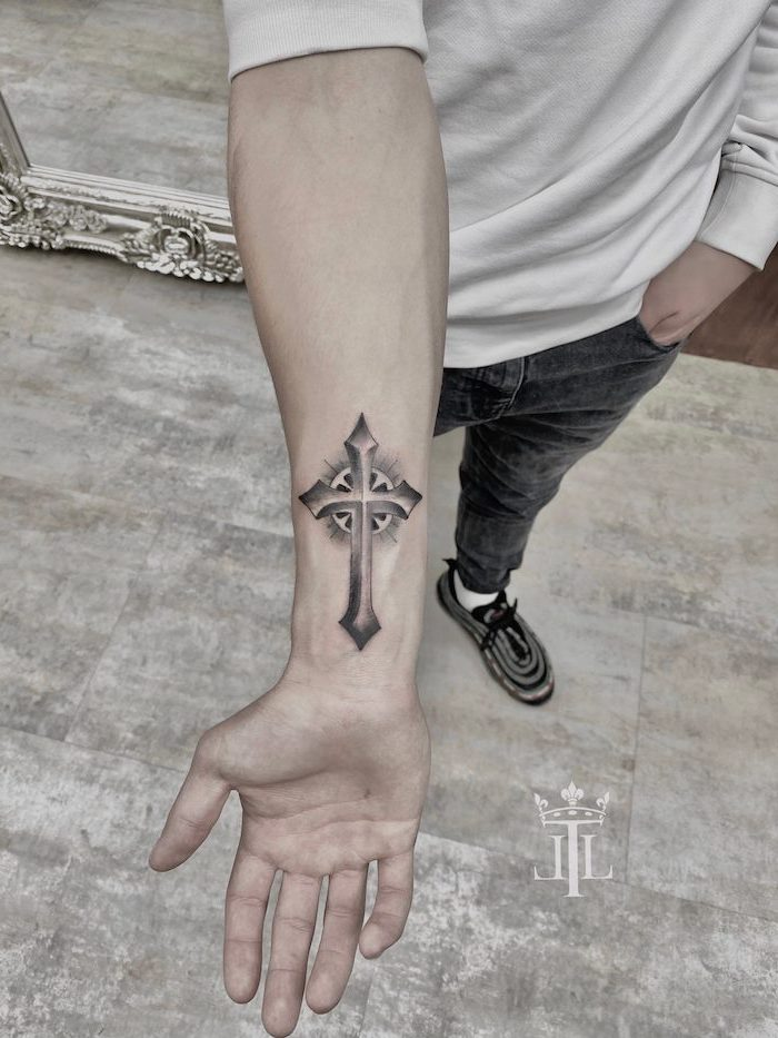 black and white cross tattooed on the wrist of man wearing jeans white blouse tattoos that represent growth