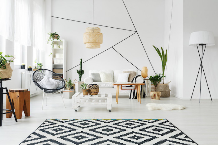 black and white geometrical carpet scandinavian minimalism white sofa black armchair wooden coffee table white walls