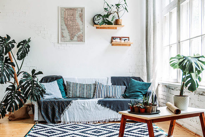 black and white rug on wooden floor scandinavian living room sofa covered with blanket in front of white brick wall