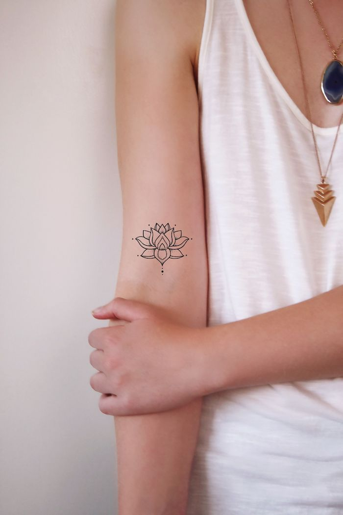 black and white small lotus forearm tattoo tattoo ideas with meanings on woman wearing white top