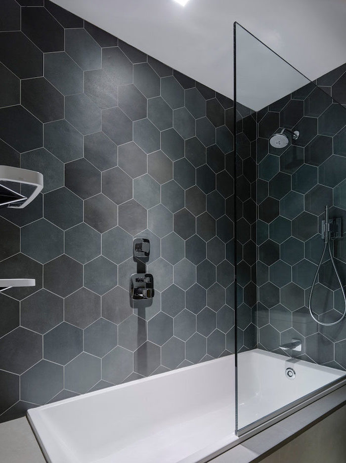 black honeycomb tiles in different shades on the shower walls separated with a glass bathroom wall tile ideas