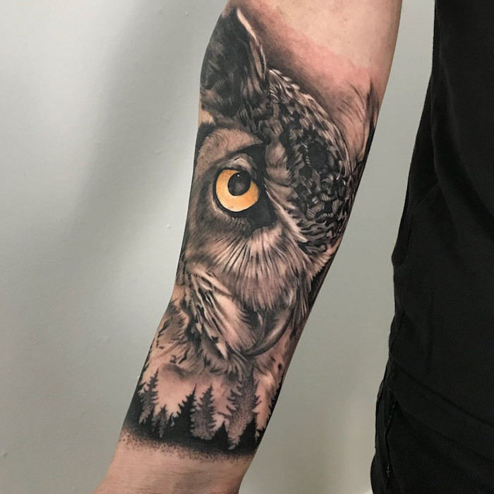 black jeans and t shirt worn by man with forearm tattoo ideas for men owl with yellow eyes above forest landscape