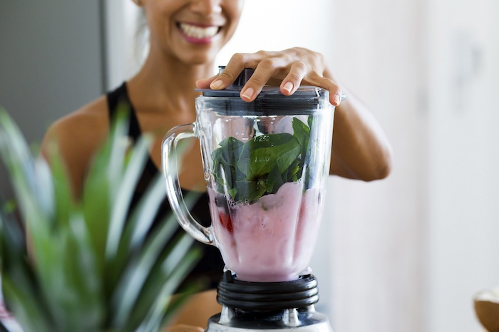 blender filled with ingredients for smoothie best detox cleanse lid held by woman wearing sports bra