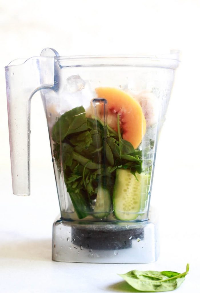 blender jug filled with ingredients best detox cleanse for weight loss cucumber peach spinach parsley
