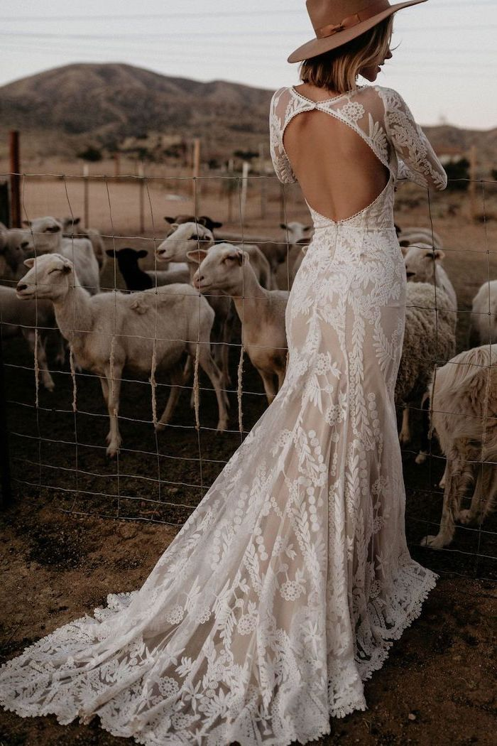 blonde woman standing next to sheep wearing dress made of lace with bare back bohemian style wedding dresses