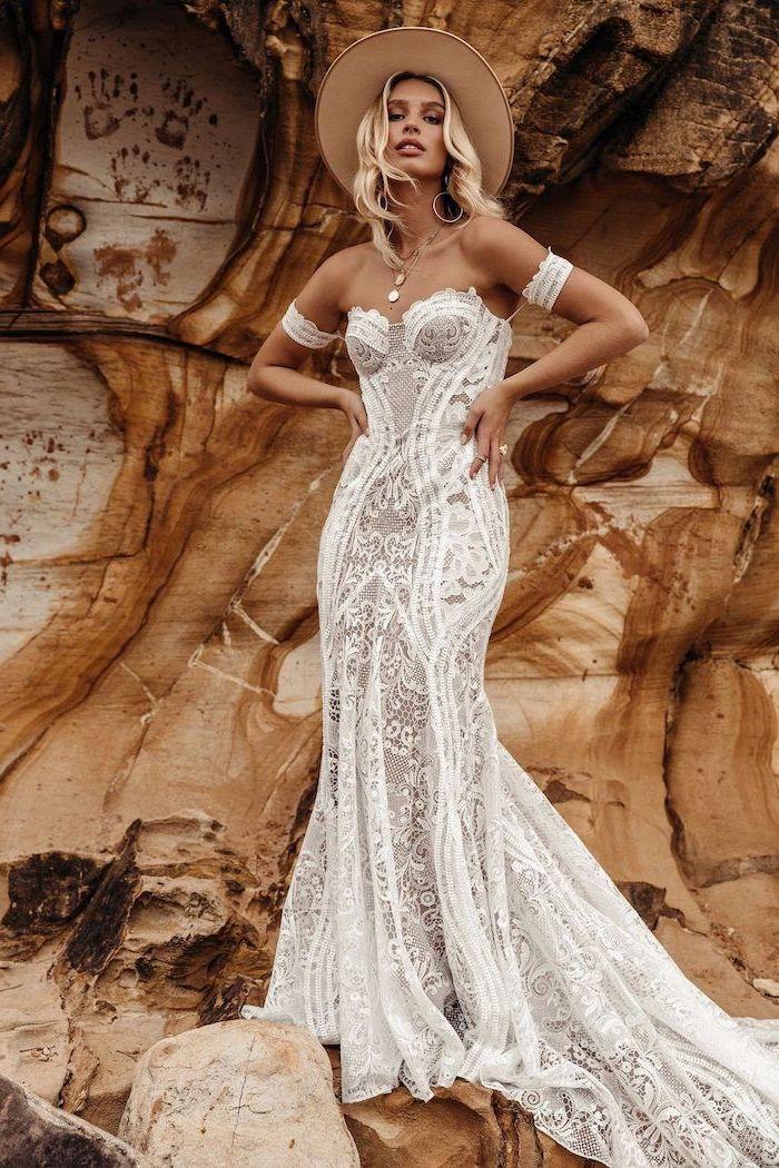 blonde woman wearing all lace dress with heart shaped neckline bohemian wedding dress wearing a baige hat standing on rocks