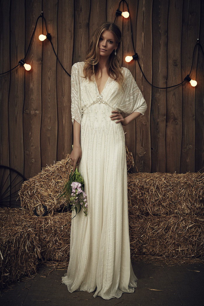 blonde woman wearing vintage long sleeve boho wedding dresses made of lace and tulle holding small bouquet made of pink flowers