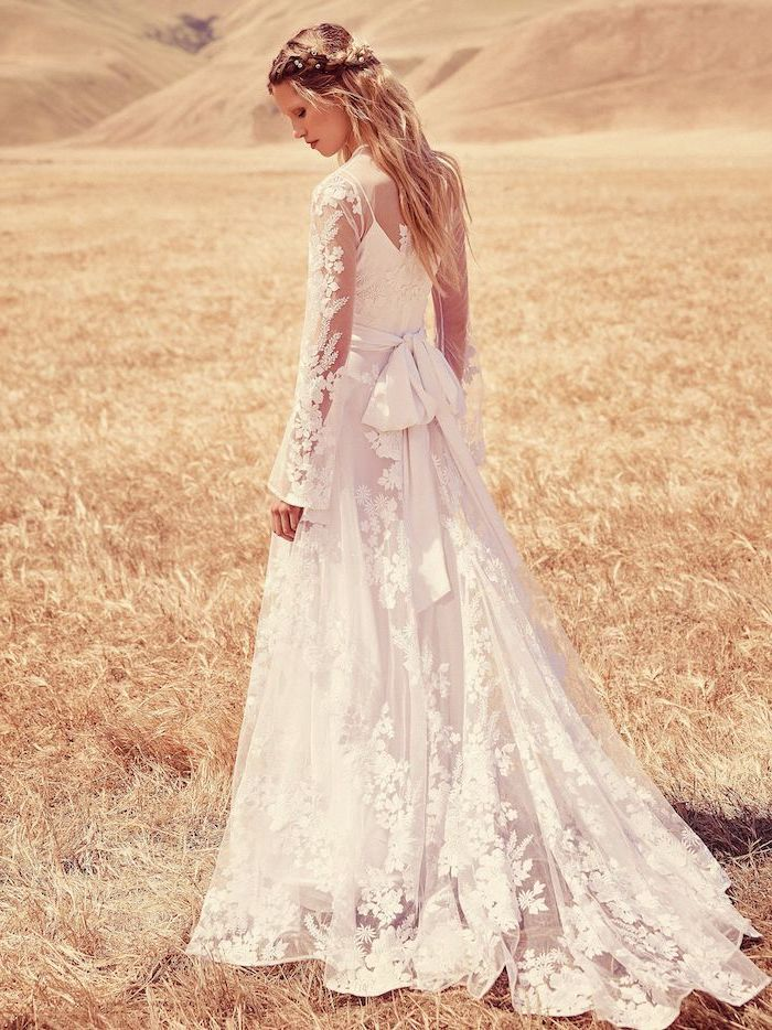 blonde woman with long wavy hair wearing lace boho wedding dress with long sleeves standing in the middle of field