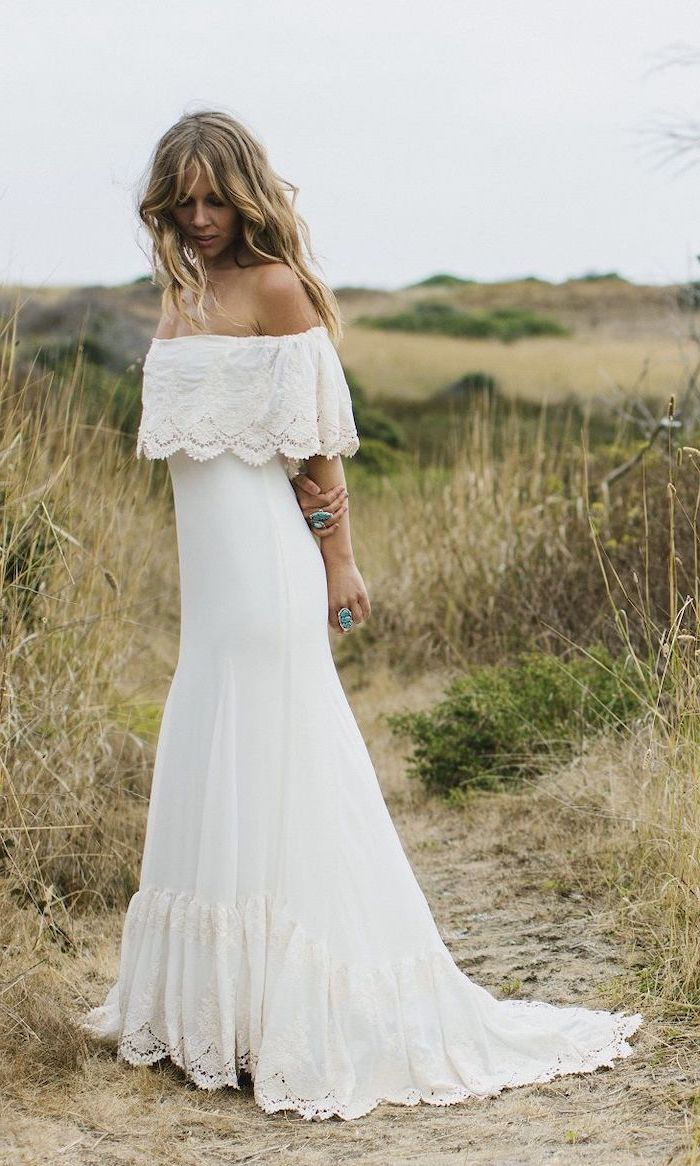 blonde woman with long wavy hair wearing long white bohemian wedding dress with lace on the bottom and lacy flounce