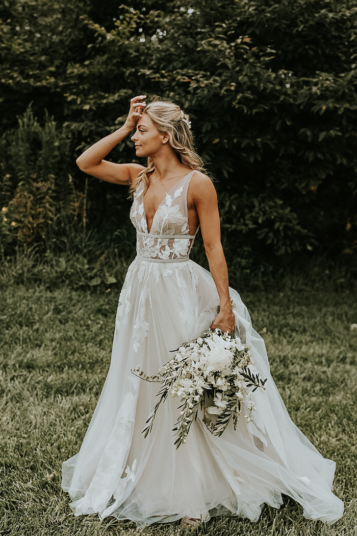 blonde woman with wavy hair wearing dress made of tulle with lacy flowers on it boho wedding dress holding white flower bouquet