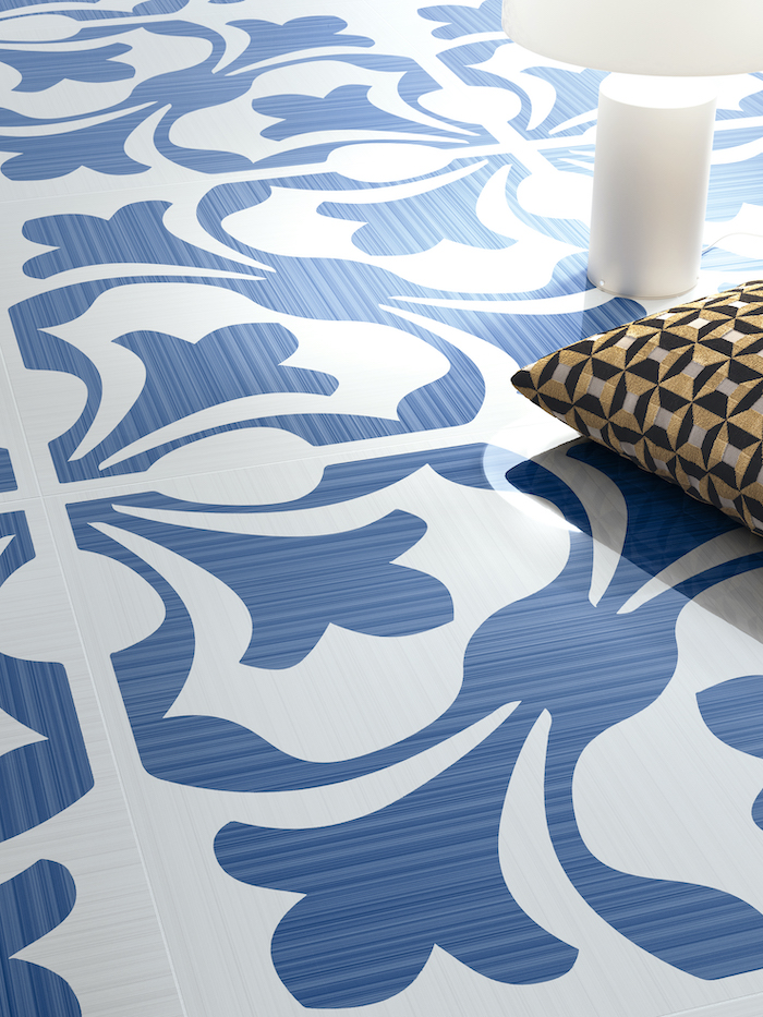 blue and white printed tiles on a floor floor tiles candle and gold and black throw pillow on the floor