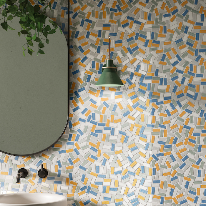 blue gray orange white mosaic tiles on wall with mirror hanging on it above sink floor tiles green lamp